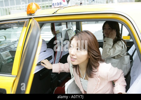 Close up of a young woman and her friend using a mobile phone in a car - Stock Photo