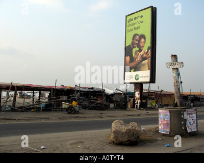 GLO pre pay phone card advertising and shanty bar on beach side road in Lagos - Stock Photo