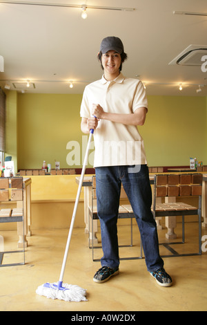 Portrait of a waiter cleaning the floor in a restaurant and smiling