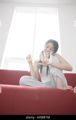 Low angle view of a young woman filing her fingernails and talking on a mobile phone - Stock Photo