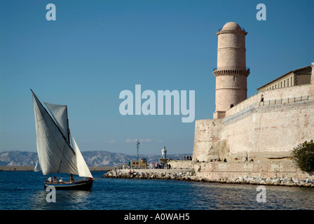 Marseille, France - Fort Saint-Jean and a sailboat with a lateen sail or latin-rig - Stock Photo