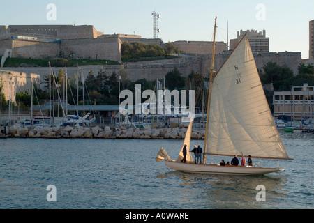 Marseille Saint Nicolas Fort And A Latin Sail Sailboat Entering Vieux Port, France - Stock Photo