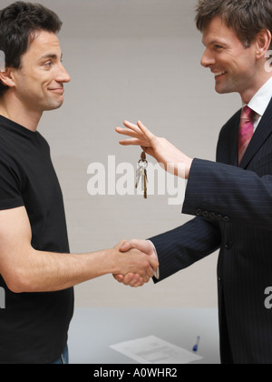 Men shaking hands and exchanging keys - Stock Photo
