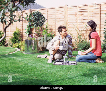 Young couple having coffee in the garden - Stock Photo