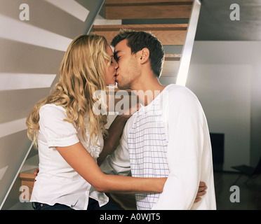 Couple kissing on staircase - Stock Photo