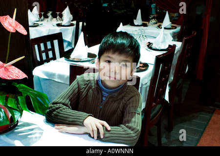 PARIS France, Portrait Young Chinese French boy Sitting at Table in Restaurant,  looking at camera, immigrants Europe - Stock Photo