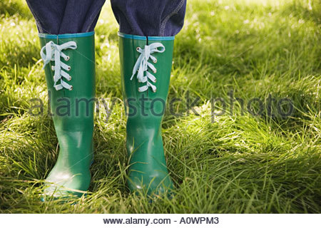 A person wearing green rubber boots - Stock Photo