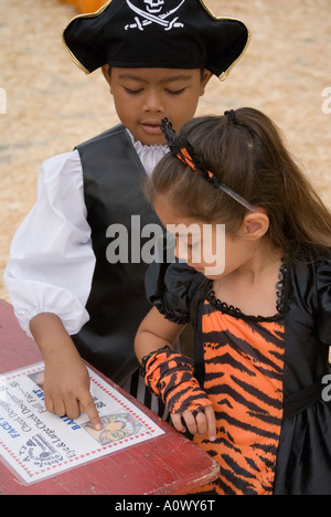 Portrait of young girl and boy looking at prices - Stock Photo