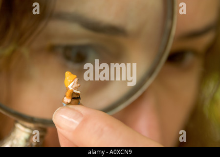 Woman inspecting a tiny gnome with magnifying glass - Stock Photo