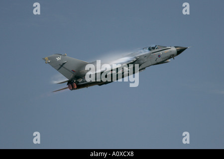 RAF Tornado GR4 flies against blue sky with wing vapour vortices - Stock Photo