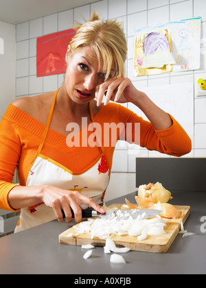 Woman chopping onions and crying - Stock Photo