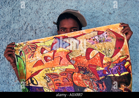 CUBA HAVANA Hip Hop graffiti artist Yulexis Garcia holds his art work to the camera - Stock Photo