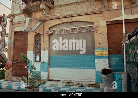 Nicosia, Cyprus. Green Line, shop abandoned in 1974. Greek Cypriot soldier stands guard at his post, rifle in view - Stock Photo