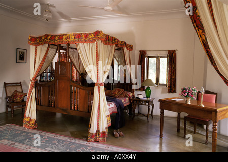Reproduction colonial style four poster bed and block printed fabrics in guest bedroom Samode Haveli Gangapol District - Stock Photo