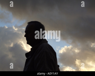 backlit person against dramatic sky - Stock Photo