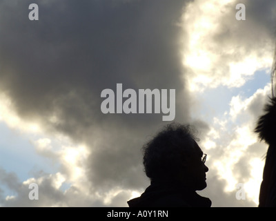 backlit people against dramatic sky - Stock Photo