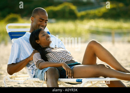 Young African couple relaxing on the beach together - Stock Photo