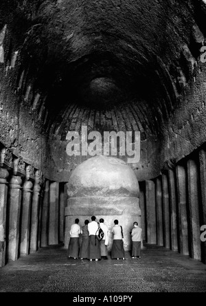 Rear view of Monks praying in front of a sculpture, Kanari Cave, Mumbai, Maharashtra, India - Stock Photo