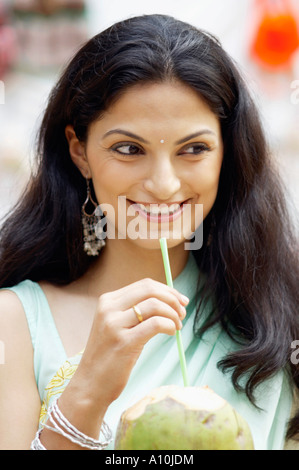 Close-up of a young woman holding a coconut with a straw - Stock Photo