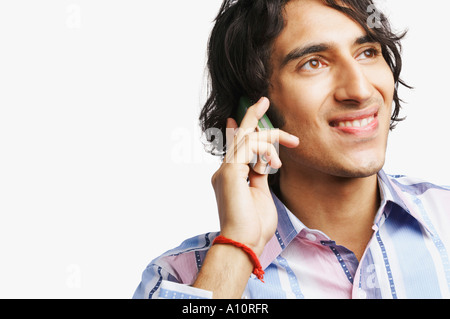 Close-up of a young man talking on a mobile phone - Stock Photo