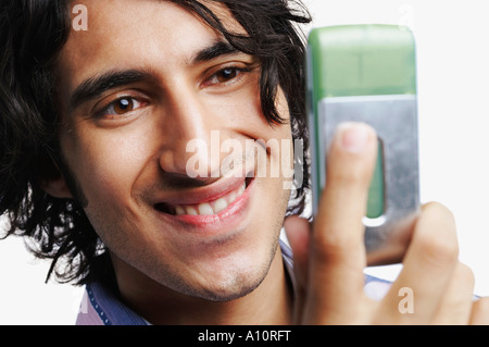 Close-up of a young man looking at a mobile phone - Stock Photo