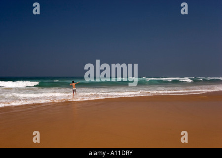 A child going to plunge himself into the surf on Cordoama beach. Enfant courant se jeter dans les vagues de la plage - Stock Photo