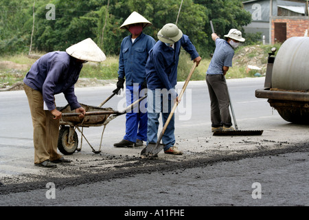 Workmen shovel in advance of the steamroller during  construction on the road from Saigon (HCMC) to the Mekong  - Stock Photo