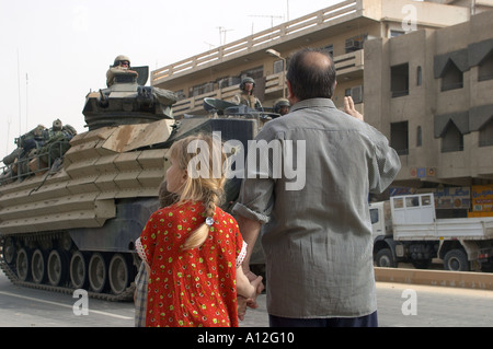 9 April 2003 Bagdad Iraq Marines roll into central Bagdad to the cheers of crowds of iraqis including this family - Stock Photo
