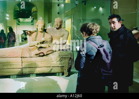 Paris France Couple Visiting in 'Louvre Museum''The Etruscan Sarcophagus of a Married Couple' Sculpture - Stock Photo