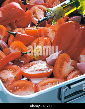 tomatoes chilies and red onions in a roasting tray - Stock Photo