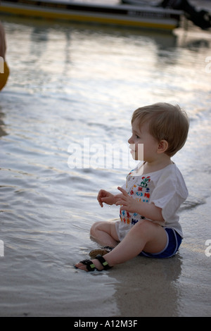 Baby boy learns to swim Mexican Riviera coast model released beach ecology cancun akumal mexico ecosystem environment - Stock Photo