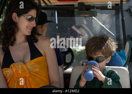 Boy and mother in golf cart at beach model released beach ecology cancun sunglasses green akumal mexico ecosystem - Stock Photo