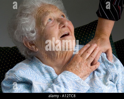 ELDERLY CARE CARER HAND COMFORT Contented smiling senior old age elderly woman looks up and touches comforting hand - Stock Photo
