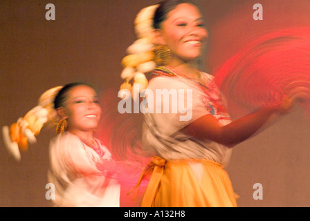 Two Mexican Dancers in costume waving fans in blurred motion - Stock Photo
