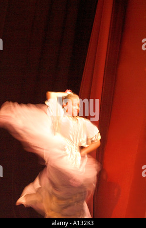 Young dancer in white twirling long skirt in front of red curtain - Stock Photo