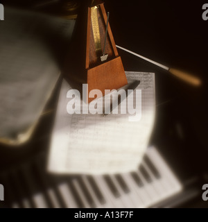 musical still life with piano sheet music and metronome - Stock Photo