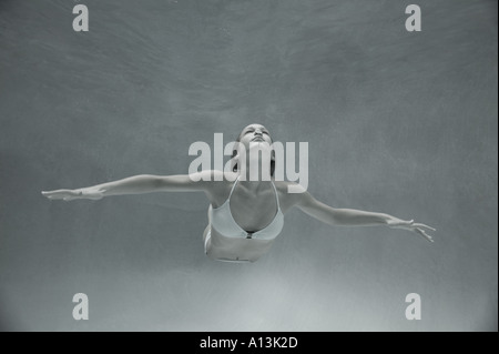 Young woman free diving in shallow water - Stock Photo