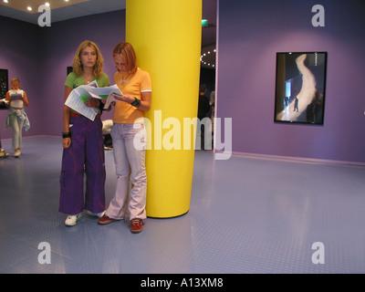 Two teenage schoolgirls doing assignment in Groninger museum Netherlands - Stock Photo