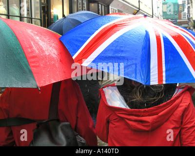 seeking shelter from the rain under Union Jack umbrella - Stock Photo