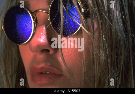 Close up of a woman wearing reflective sunglasses with water drops on the lenses - Stock Photo