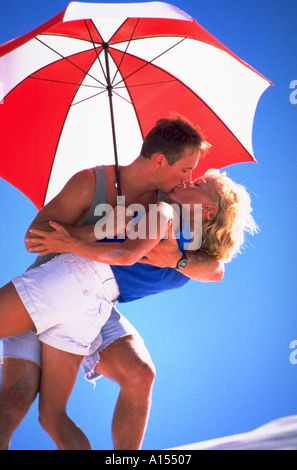 A man and woman kissing passionately in the shade of a red and white umbrella - Stock Photo