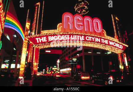 The main sign over the road leading into Reno Nevada shines brightly at night - Stock Photo