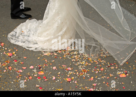 Horizontal close up of organic rose petal confetti on the ground after being thrown at the bride and groom at a - Stock Photo