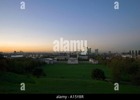Horizontal wide angle view at sunset across Greenwich Park with the Canary Wharf skyline in the background. - Stock Photo