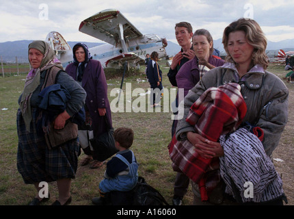Newly arrived ethnic Albanian refugees from Kosovo wait for humanitarian workers to bring them to a tent at the - Stock Photo