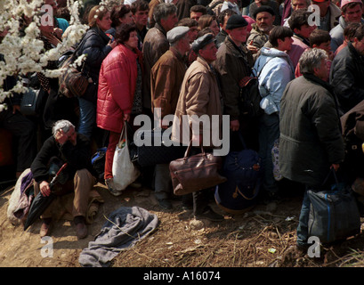 Ethnic Albanian refugees from Kosovo wait to board buses at the massive camp in Blace Macedonia Tuesday April 6 - Stock Photo
