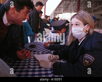 Ethnic Albanian refugees from Kosovo are processed by Macedonian police before they were put on a plane to Turkey - Stock Photo
