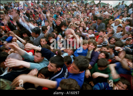 Ethnic Albanian refugees from Kosovo rush to get goods from the Italian Nato forces in the Stenkovec camo near Skopje - Stock Photo