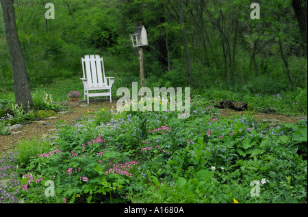 Shade garden with white Adirondack chair and whimsical birdhouse in home backyard garden, Midwest USA - Stock Photo