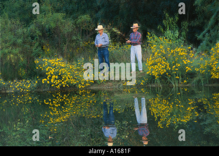 Two older men, brothers, fishing side by side, on a summer evening in rural pond with wildflowers, Missouri USA - Stock Photo